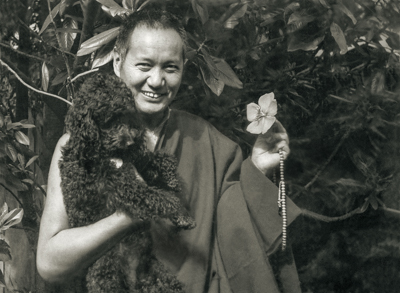 Lama Yeshe and Bobik in Beatrice Ribush's backyard, Melbourne, Australia, 1974. Photo: Dorian Ribush.