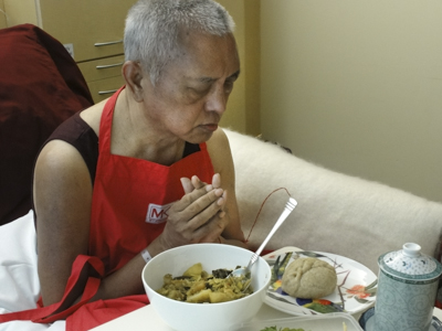 Rinpoche offering food while in hospital in Australia after manifesting a stroke in April 2011. Photo: Ven. Holly Ansett.