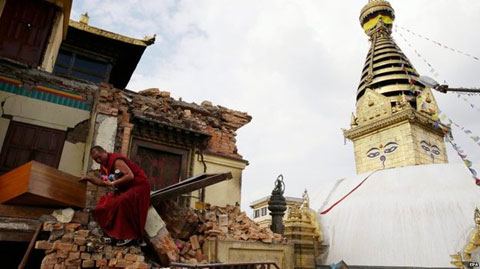 A monk salvages items from the rubble of a building next to the Boudhanath temple complex. Photo: AP.