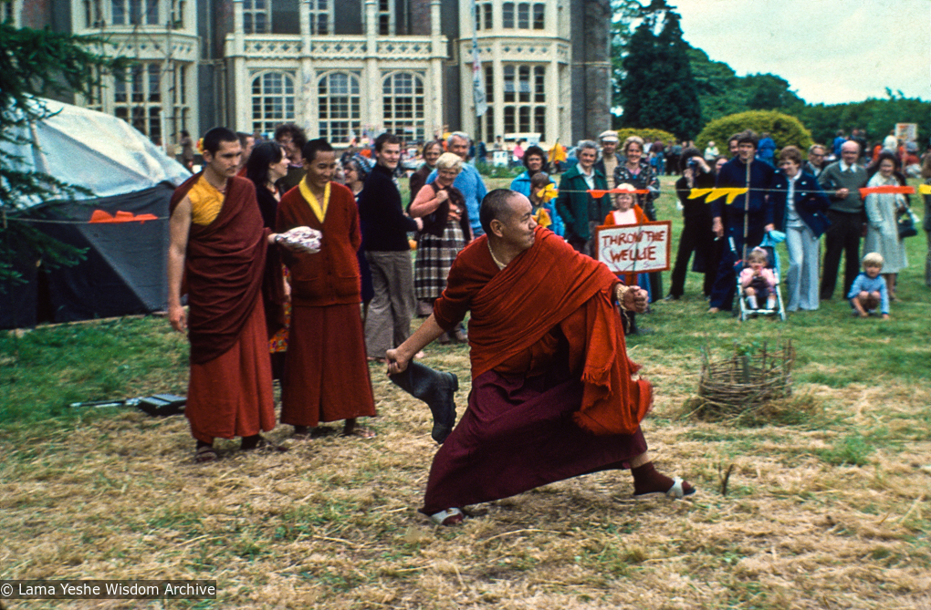 """(16697_sl.psd) Among the games staged in the gardens was the rural sport of """"wellie wanging."""" This consisted of hurling a large rubber Wellington boot as far as possible, from a standing position. Chris Kolb (Ngawang Chotak) and Ven Samten watch Lama Yeshe taking his turn, Festival Day at Manjushri Institute, England, 25th of August, 1979. Brian Beresford (photographer)"""