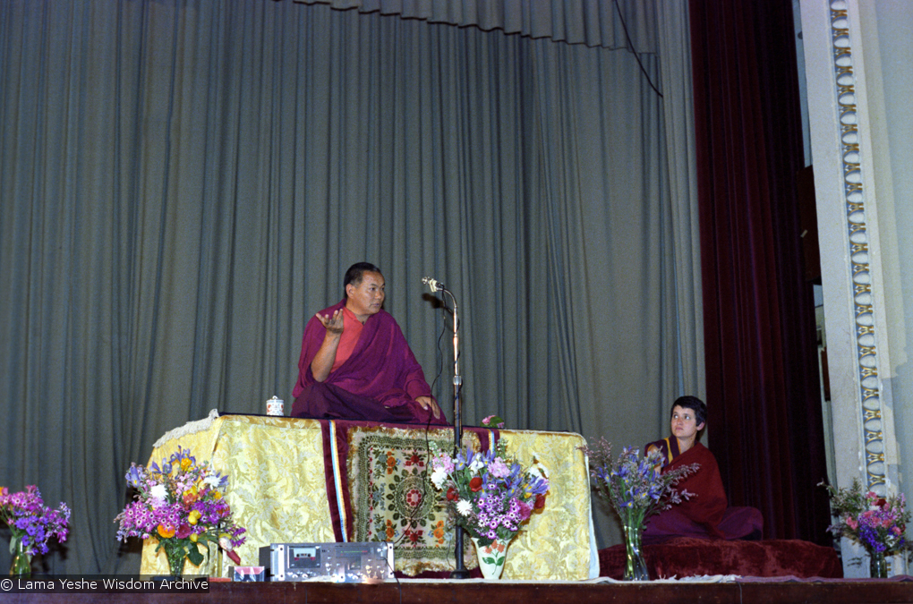 (22156_ng.tif) Lama Yeshe teaching at Malvern Town Hall, Australia, 1979, with Tara House director Bonnie Rothenberg (Konchog Donma or KD) on the right.