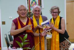Nick Ribush and Wendy Cook present LYWA's latest publication to Lama Zopa Rinpoche, 2016. Photo: Ven. Roger Kunsang.