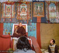 (10237_ng-3.JPG) Lama Yeshe giving final teaching at Sixteenth Kopan course, Kopan Monastery, Nepal, 1983. Karuna Cayton at the foot of the teaching throne. Photo by Wendy Finster.