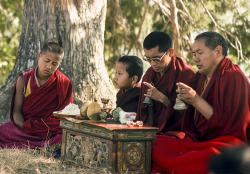 (12736_sl-2.psd) Lama Yeshe and Lama Zopa Rinpoche doing puja (spiritual practice) with Tenzin Norbu under the tree, Kopan Monastery, Nepal, 1976. Photo by Jon Landaw.
