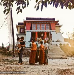 (13288_pr-2.psd) Lama Yeshe at entrance to Kopan with Sister Max Mathews during Fourth Meditation Course, 1973. On the left is Bill Searle holding his son, Adam. Photo by Christine Lopez.