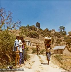 (13298_pr-2.psd) Villagers carrying wood while westerners watch, road to Kopan Monastery, Nepal, 1973. The monastery is on the hilltop to the right. Photo by Christine Lopez.