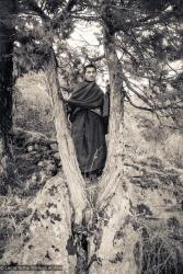 (15149_ng.tif) Lama Zopa Rinpoche posing in a tree, Lawudo Retreat Centre, Nepal,1972