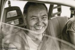 """(15264_pr-3.psd) Lama Yeshe leaving Geneva, Switzerland, 1983. Jan-Paul Kool (photographer): """"I had taken a lot of photos of Lama over the years and it seemed to me he was much more serious that time in Geneva, less laughing.  That shot of him in the car was his last big smile for me."""""""