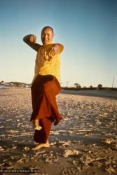 (15928_pr.psd) Lama Yeshe dancing/debating on the beach after the month-long course at Chenrezig Institute, Australia, 1975. Photo by Anila Ann.