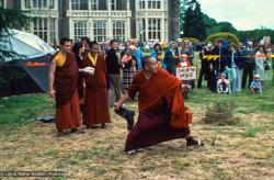 "(16697_sl.psd) Among the games staged in the gardens was the rural sport of ""wellie wanging."" This consisted of hurling a large rubber Wellington boot as far as possible, from a standing position. Chris Kolb (Ngawang Chotak) and Ven Samten watch Lama Yeshe taking his turn, Festival Day at Manjushri Institute, England, 25th of August, 1979. Brian Beresford (photographer)"