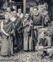 (18950_pr-3.psd) Lama Yeshe and Lama Zopa Rinpoche with students and artists, Tushita Retreat Centre, Dharamsala, India, 1973. Wim (squatting at the front right), the Dutch artist, who had painted the walls of Lawudo Gompa the year before, arrived at Tushita and painted a mural of Guru Shakyamuni on the left front porch wall of the building, while Lawrence Greenberg (standing to the right of Rinpoche) painted the four friends on the right. Suzanne Lee is standing to the left of Lama Yeshe.