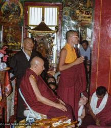 (23244_ng-3.psd) Ling Rinpoche teaching at the Tibetan Temple, Bodhgaya, India, 1982. Lozang Kunrig (Thubten Tsering- Ling Rinpoche attendant) on left, Bruno LeGuevel standing center, Lama Zopa Rinpoche seated, head lowered.