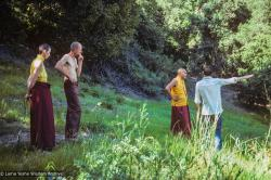 (39390_sl-3.jpg) Ann McNeil (Anila Ann), John Jackson, Lama Yeshe, and Rick Crangle surveying the land at Vajrapani Institute, California, 1978.