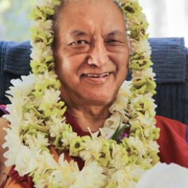 Lama Zopa Rinpoche adorned with flowers, 2010.